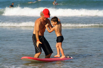 Photo of boy getting his first surfing lesson